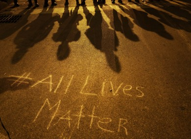 A message written on the pavement as police in riot gear cast shadows in Baltimore on 1 May.
