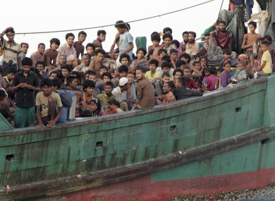 Migrants sit on their boat as they wait to be rescued this morning.