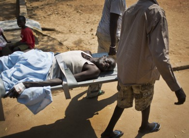 In this file photo, a man with a gunshot wound in his leg is carried by stretcher from one ward to another inside the Juba Military Hospital in Juba, South Sudan