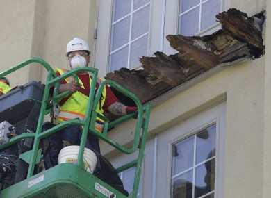 A crew works on the remaining wood of an apartment building balcony that collapsed in Berkeley.
