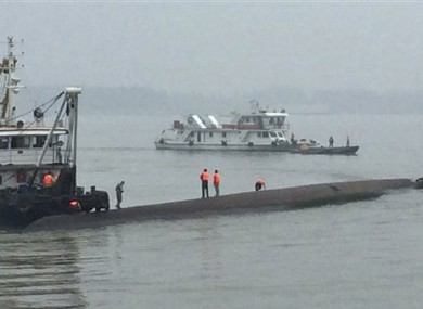 Rescue workers stand on the capsized ship.