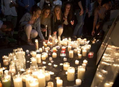 Mourners lay candles during a vigil in June.