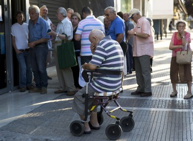 Greek pensioners queue outside a bank today.