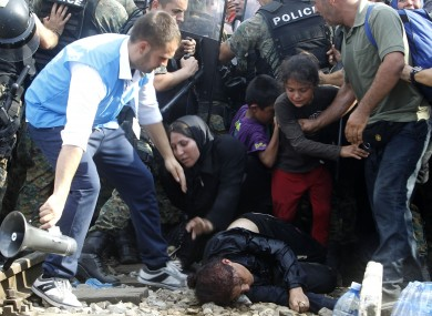 A migrant who has collapsed while the crowd of migrants were pushing the police to enter Macedonia .