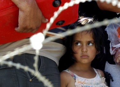 A migrant girl looks on from behind barbed wire as her family waits to enter into Macedonia.