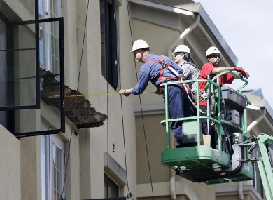 A worker measures the remains of the collapsed balcony in the aftermath of the Berkeley disaster