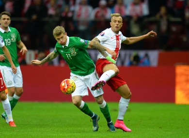 Ireland's James McClean tackles Poland's Kamil Grosicki.