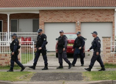 Police walk around a property in the suburb of Guildford in Sydney.