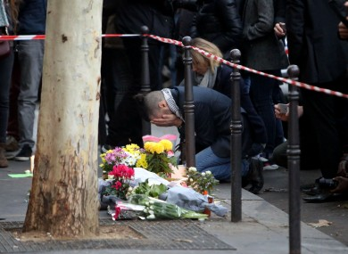 A man holds his head in his hands beside flowers paying tribute to the victims of Friday night's attacks.