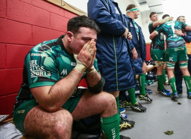 The prop sits in pain while team-mates celebrate after beating Munster.