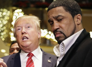 Donald Trump talks with reporters while surrounded by a group of African-American religious leaders.