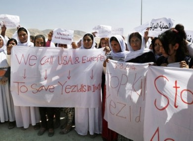 Yazidi Kurdish women hold posters and banners during a protest against the Islamic State