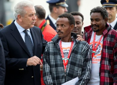 European Commissioner for Migration and Home Affairs Dimitris Avramopoulos, left, speaks to Eritrean refugees waiting to board an Italian aircraft that will take them to Sweden, at Rome's Ciampino airport in October.