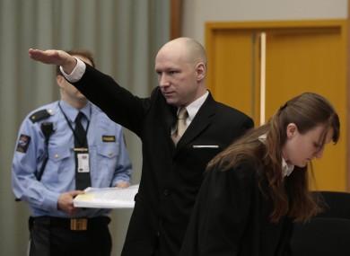Breivik gestures as he enters a courtroom in Skien.