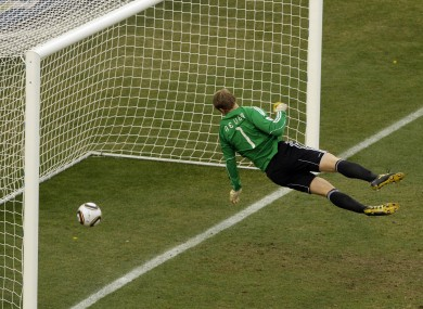 Germany goalkeeper Manuel Neuer looks at the ball that hit the bar to bounce over the line.