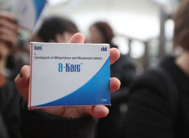 A pro-choice protester holds a box of abortion pills at Connolly Station after bringing them to Dublin from Belfast in October 2014.
