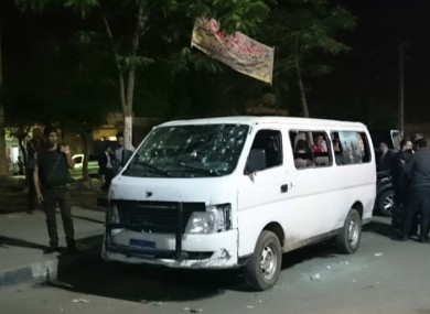 Egyptian police and civilians gather around the bullet-ridden minibus.