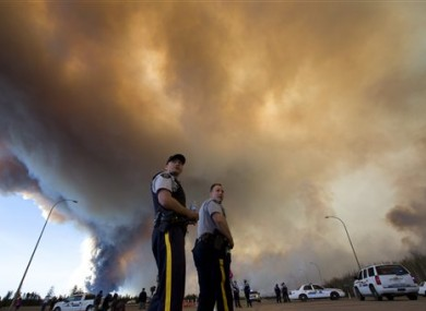 Police officers direct traffic under a cloud of smoke from a wildfire in Fort McMurray, Alberta, Canada.