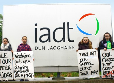Children at the school hold banners on front of Dun Laoghaire Institute of Art and Design.