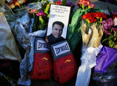 Boxing gloves and a message sit among flowers at a makeshift memorial to at the Muhammad Ali Center.