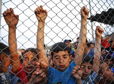 Syrian refugee children chant slogans behind a fence at the Nizip refugee camp in Gaziantep province