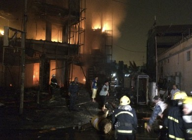 Iraqi firefighters extinguish a fire as civilians gather after a car bomb went off in Baghdad.