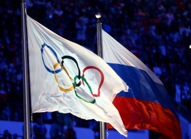 A flag bearing the Olympic rings sits next to the flag of Russia