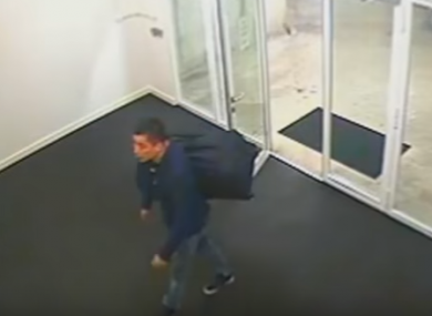 A still from PSNI footage of Juan Guan entering Obel Tower in Belfast carrying a holdall containing 15kg cannabis