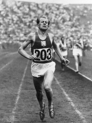 In this July 30, 1948, file photo, Czechoslovakia's Emil Zatopek breaks the tape to win the men's 10,000-meter Olympic Games race at Wembley Stadium, London.