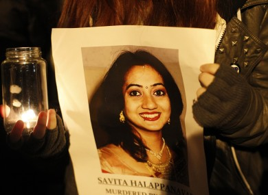 A woman holds a picture of Savita Halappanavar during a candle lit vigil outside Belfast City Hall