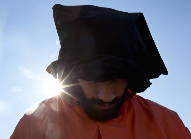 A protester wearing an orange jumpsuit depicting a Guantanamo Bay detainee, participates in a rally outside of the White House in Washington in January.