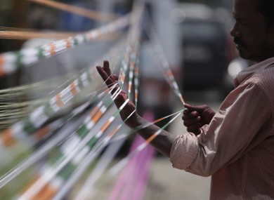 A man prepares threads with the three colors of the Indian flag for flying kites on India's Independence Day.