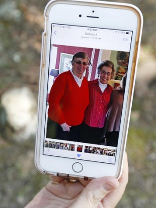 Jamie Sample, a parishioner of St. Thomas the Apostle Catholic Church in Lexington, Miss., sits in the shade in Durant, Miss., and shows a smartphone photograph taken last December 2015, of Sisters Paula Merrill, left, and Margaret Held.