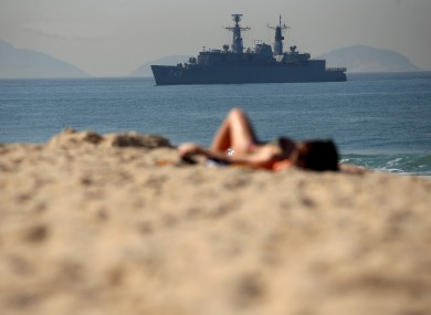 Sunbathers relax on the Copacabana beach as the Brazilian navy provides security at sea at the Olympic Games in Rio de Janeiro.