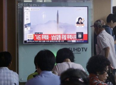 A man passes by a TV news program with a file footage about North Korea's rocket launch yesterday.