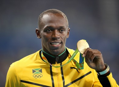 Jamaica's Usain Bolt receives the gold medal for the Men's 100 Metres at the Olympic Stadium.