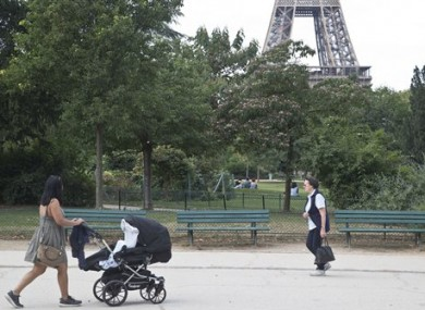 People walk in the Champ de Mars garden near the Eiffel Tower, beside the spot where a woman was allegedly raped earlier this week.