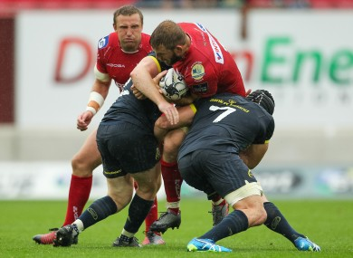 Munster's Niall Scannell and Tommy O'Donnell tackle John Barclay during last weekend's game against Scarlets.