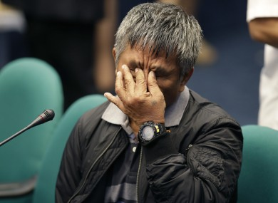 Former Filipino militiaman Edgar Matobato pinches his nose during a break of testimony at the Philippine Senate today.
