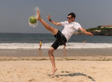 Life's a beach: McKillop playing football on Copacabana last week.