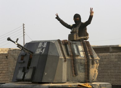 A member of Iraq's elite counterterrorism forces in a military convoy flashes a victory sign.