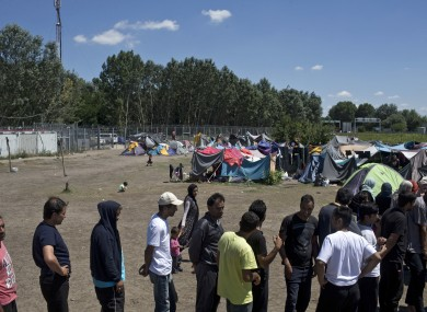 People queue to receive aid packages at a makeshift migrant and refugee camp situated meters away from the Serbian border with Hungary.