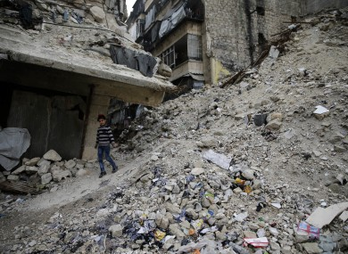 A Syrian girl walks amid the wreckage of damaged buildings and shops in the western city of Aleppo.