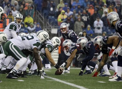 Players from the New York Jets and New England Patriots about to collide at the line of scrimmage.