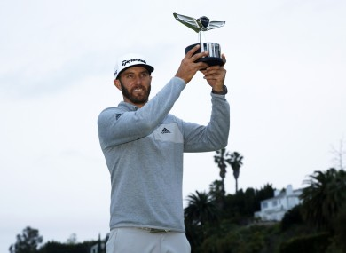 Johnson posing with his trophy on the 18th green.