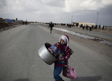 A displaced girl in Mosul crosses the road at a military checkpoint yesterday.
