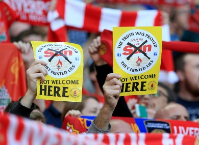 Liverpool fans hold up 'Shun the Sun, Not Welcome Here' fliers during a Premier League match at Anfield last September.