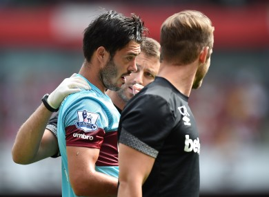 West Ham defender James Tomkins is helped off the pitch by medical staff after a clash of heads with Arsenal's Olivier Giroud.