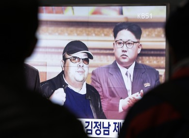 A TV screen shows pictures of North Korean leader Kim Jong Un (R) and his older brother Kim Jong Nam (L).