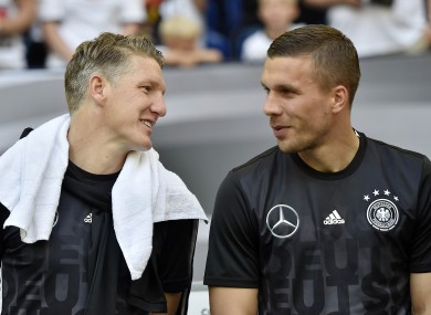 Payday: Podolski, right, with German team-mate Bastian Schweinsteiger of Manchester United.